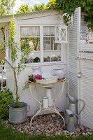 Vintage Waschschüssel und Krug in rostigem Metallgestell vor Gartenhäuschen