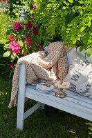 Gebäckschale und Kuchenteller neben Häkeldecke auf weisser Holzbank im Garten