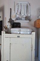 Vintage Brotbehälter aus weiss lackiertem Metall auf ländlichem Schränkchen, oberhalb Schöpfkellen