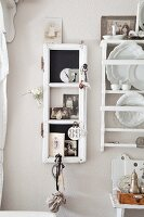 Narrow display case hung on pastel wall next to white decorative plates in plate rack