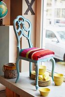 A Baroque-style chair with a colourful knitted cushion cover