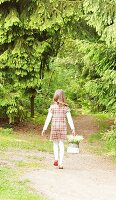 Little girl carrying basket of lily-of-the-valley along woodland path
