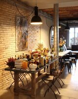 Vintage pendant lamps above groceries on table in rustic interior with exposed brick wall