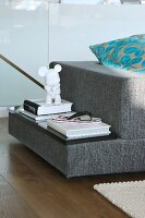 Stacked books and ornaments on upholstered shelf integrated into designer sofa