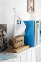 A sailing boat made from driftwood as a book end on a shelf