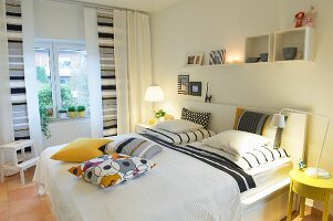 Curtains and cushions with geographic grey and yellow patterns adding a friendly designer touch to a white bedroom