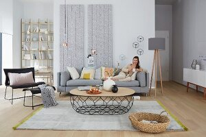 A woman reading on a sofa in a seating area in light grey tones with copper accents against wallpapered wood panels
