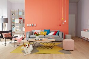 A seating area with brightly coloured pendant lamps against a coral-coloured, a mustard yellow rug and cornflower-blue cushions