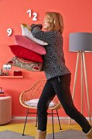 A woman walking past a coral-coloured wall with a stack of cushions with a simple floor lamp and a retro-style wicker chair in the background