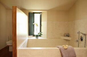 Large bathtub in corner of bathroom below window and toilet behind screen