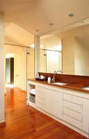 Designer bathroom with fitted washstand, white base units and mirrored wall