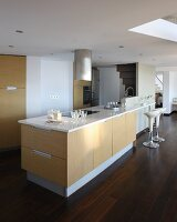 Island counter with breakfast bar in designer kitchen below mezzanine