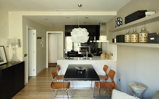 Table with black top and wooden shell chairs in front of counter in open-plan kitchen