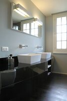 Black, curved washstand with white countertop basins and wall-mounted taps below illuminated mirrors on grey-painted wall