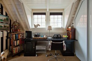 Desk, classic Eames swivel chair and other small items of furniture next to bookcase in attic room