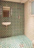 Modern bathroom with floor-level shower and green and white, geometric tiles