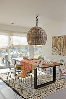 Pendant lamp with wicker lampshade above dining area with colourful, vintage metal chairs