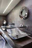 Two curved chrome basins on solid wooden washstand against stone-tiled wall