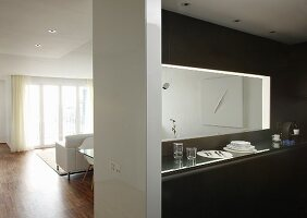 Hatch above narrow counter in designer kitchen with view into white-furnished interior