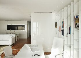 Home office area in open-plan interior with white furnishings, Eames Aluminium Chairs and fitted shelving