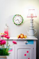 Wall clock decorated with colourful fabrics and neon green pompoms, vintage sideboard and table lamp made from stacked porcelain crockery