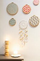 Embroidery frames covered in colourful fabrics and hand-crafted dreamcatcher hung on wall