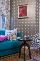 Antique side table in front of light blue couch against patterned wallpaper