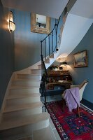 Writing desk, armchair and Oriental rug under curved staircase