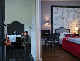 View through open doors into bedroom and ensuite bathroom with black marble floor
