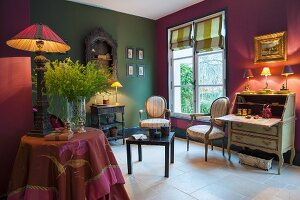 Writing desk, chairs and side tables in lounge with walls in different colours