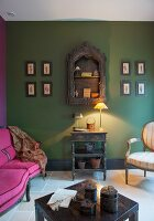 Pink sofa, lamp on console table and green-painted wall in lounge