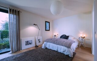 Frameless bed and two silver metal bedside tables in minimalist bedroom