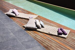 Quilted mats with cushions on wooden deck adjoining modern pool