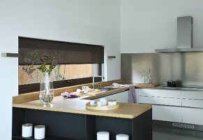 Elegant fitted kitchen with wooden worksurface and stainless steel splashback