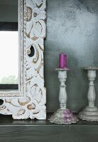 Detail of mirror with ornate, floral wooden frame and vintage-style candlesticks