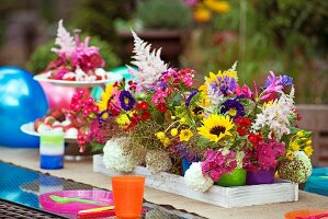 Colourful beakers of summer garden flowers decorating table