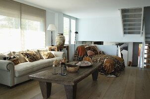 Rustic wooden coffee table, pale sofa and chaise on mezzanine level