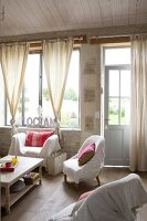 Various armchairs with white loose covers around coffee tables in front of large window with knotted curtains in simple living room