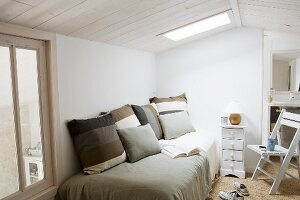 Striped cushions on bed below skylight in simple room
