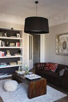 Pendant lamp with black lampshade above seating area with retro leather sofa and coffee table made of solid, exotic wood
