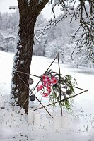 Star made from twigs decorated with baubles and ribbon leaning against tree and lit candles in snowy landscape