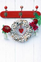 Wreath of seashells decorated with zinnia, dahlia and snap dragon hung on vintage coat rack