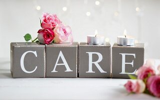 Pink rose buds and tealights on card cubes with decorative lettering spelling 'CARE'