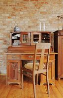 Biedermeier chair at antique writing desk against exposed brick wall
