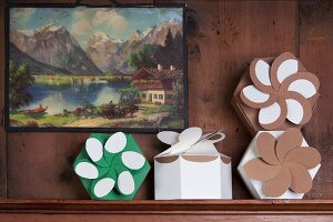 Hexagonal folded gift boxes with floral rosettes on narrow window ledge below traditional landscape painting on wood-panelled wall