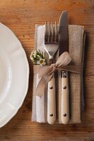 Cutlery and linen napkin tied with ribbon and decorated with waxflowers