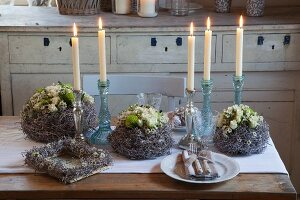 Romantic wreath of waxflowers, green chrysanthemums and cream polyantha roses amongst lit candles in candlestick on rustic table