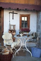 White vintage garden table and sheepskins on garden chairs outside farmhouse; potted heather and pine cones on table