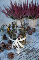 Tealight holder decorated with twigs and lichen in front of pink heathers