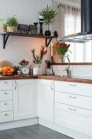 Festive flower arrangements on white kitchen counter and house lanterns on bracket shelf